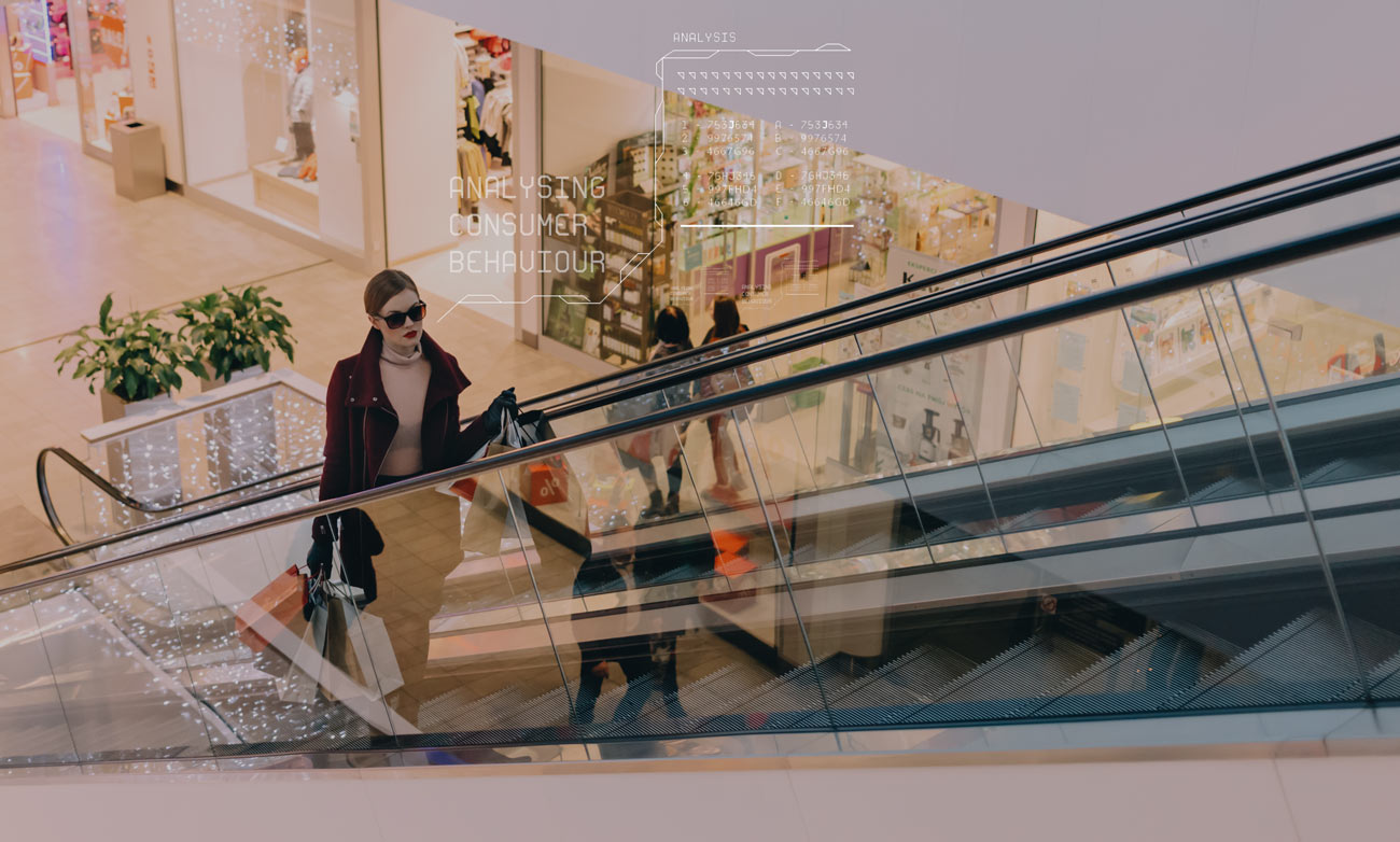 woman on escalator in shopping centre carrying bags